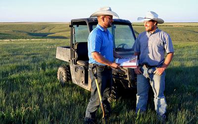 Two ranchers in a pasture reviewing a mangement plan.