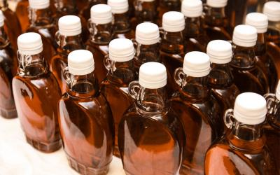 Bottles of maple syrup arranged on a table.
