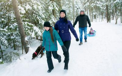 Family walking through a snow-covered, wooded trail.