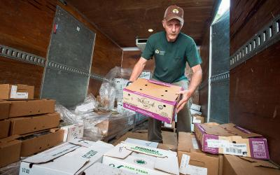 Producer unloading fresh, farm-grown produce from a delivery truck at a super market.