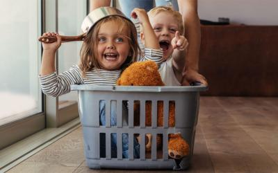 Mother pushing laundry basket along the floor with two children riding inside it.