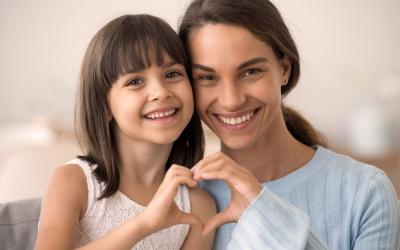 Daughter and happy mother join hands in heart shape.