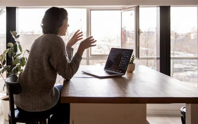 Young woman participating in a video conference at a remote work station.