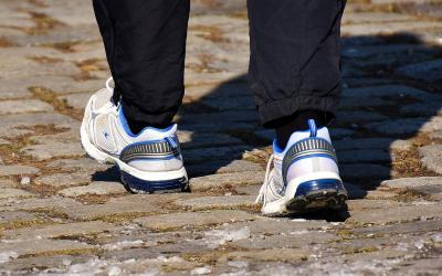 Person walking outdoors wearing a pair of comfortable walking shoes.