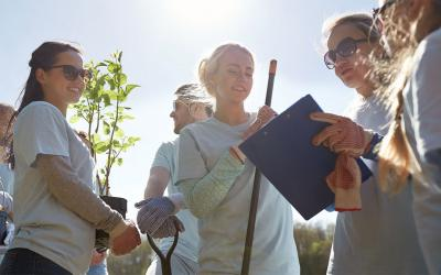 Woman with clipboard instructing a group of volunteers in a community garden.